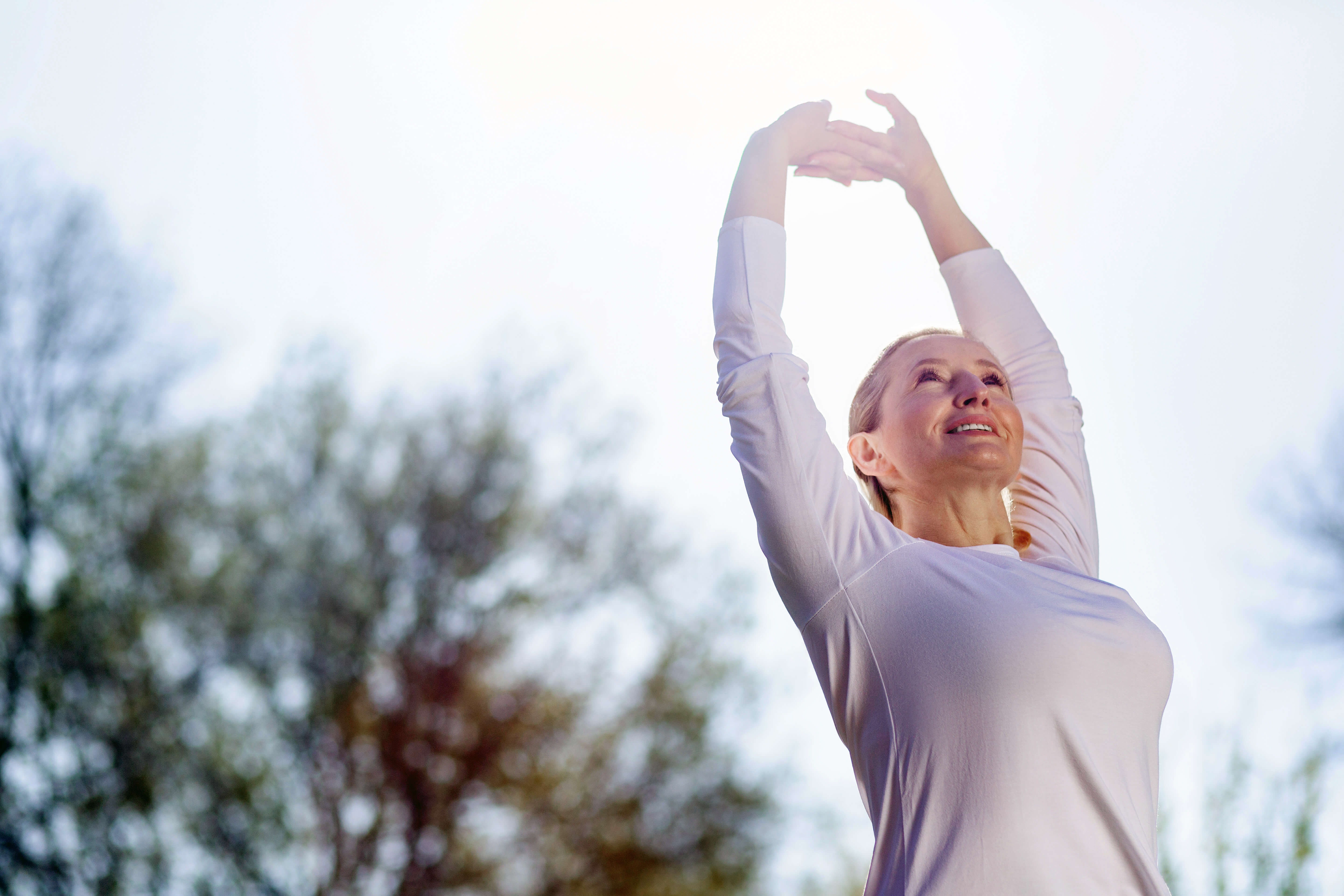 middle-aged-lady-stretching-with-hands-up-to-the-sky